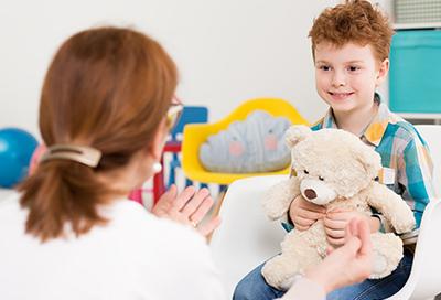 Smiling boy holding a teddy bear