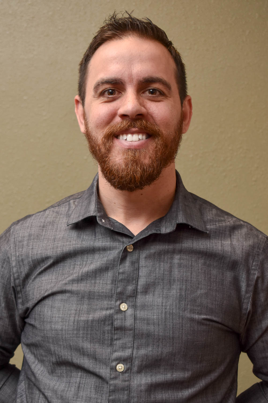 Josh Hamman - White smiling male with brown hair and beard.