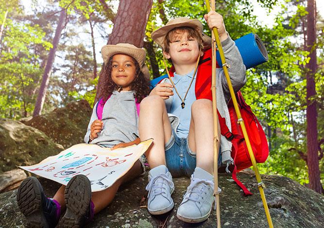 A girl a boy sit on a rock holding a map.