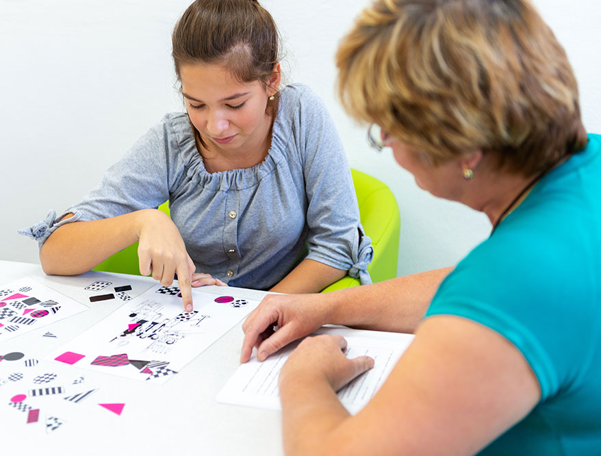A behavior technician works with a teenage girl.